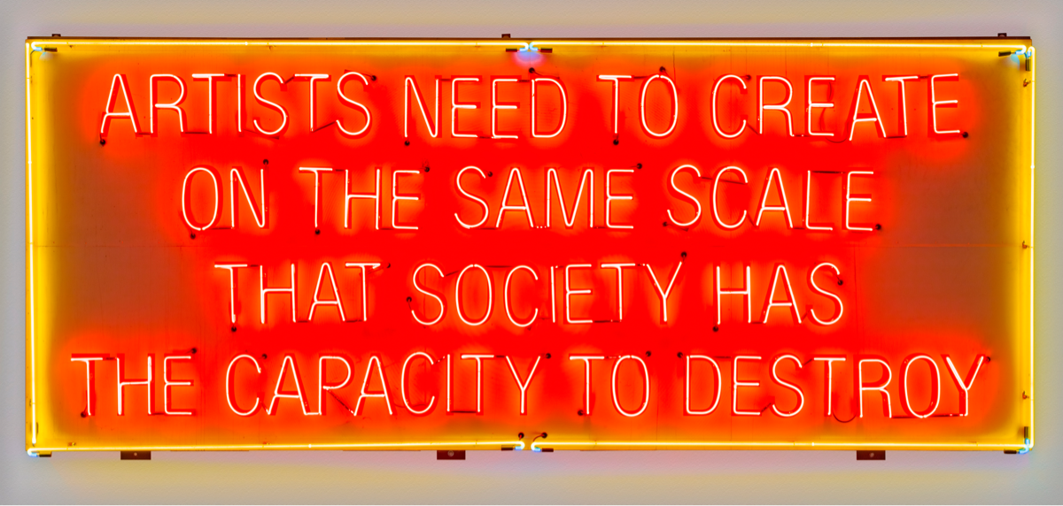 A red neon sign that says, Artists Need to Create on the Same Scale that Society Has the Capacity to Destroy, by artist Lauren Bon